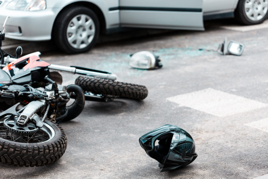 Overturned motorcycle and helmet on the street after collision with the car